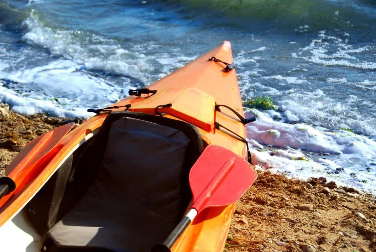 Kayak and paddle on the river bank