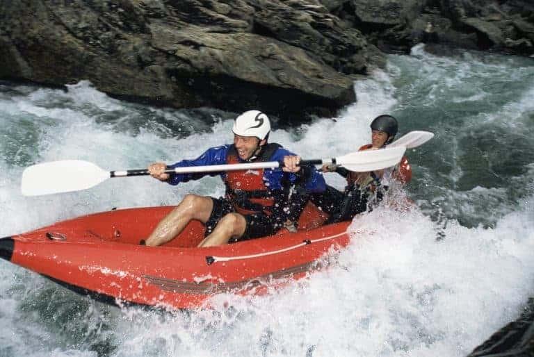 best inflatable kataks - man paddles in orange inflatable in rapids