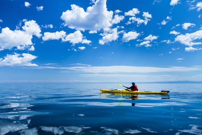 Yellow touring kayak on open blue lake